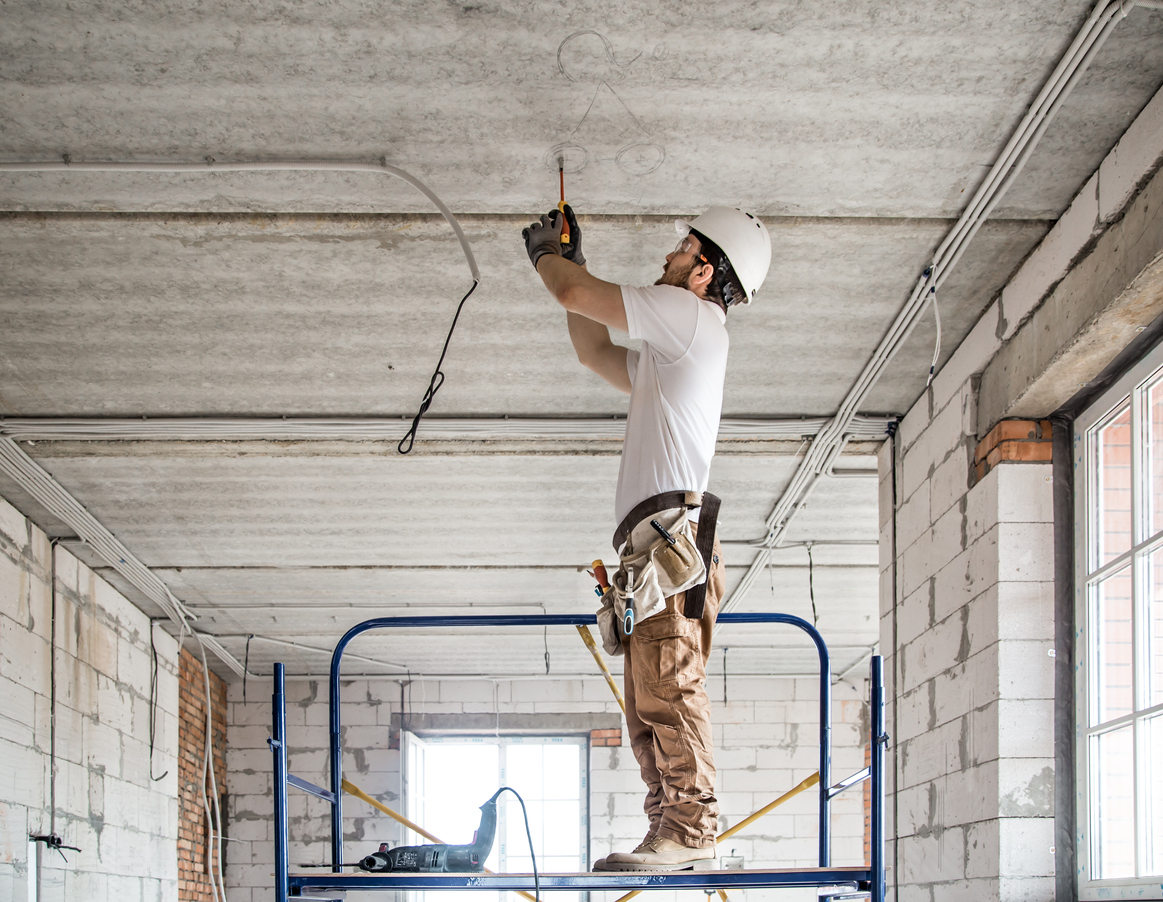 Electrician installer with a tool in his hands, working with cable on the construction site. Repair and handyman concept. House and house reconstruction.